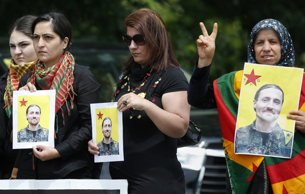 Members of  the New England Kurdish Association hold pictures of Keith Broomfield outside the Grace Baptist Church in Hudson, Mass., after his funeral service Wednesday.
