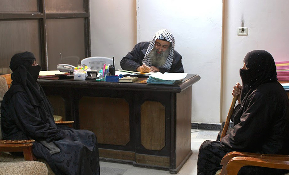 In this photo released on Feb. 10 by a militant website, two women sit in the office of an Islamic State group judge, center, at an Islamic court in al-Tabqa town in Raqqa City, Syria.