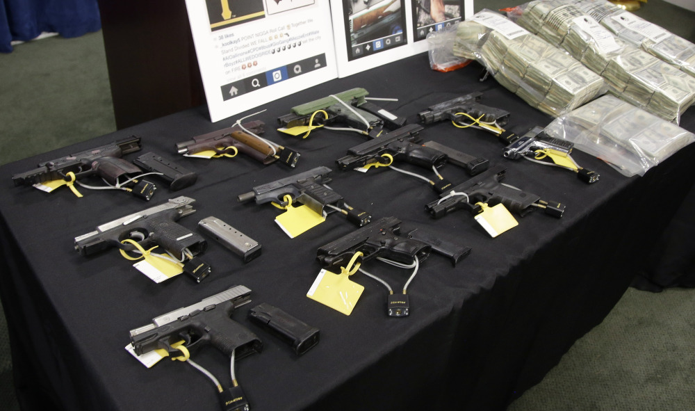 Weapons and money collected during a gang roundup are displayed at a news conference Thursday in Boston.