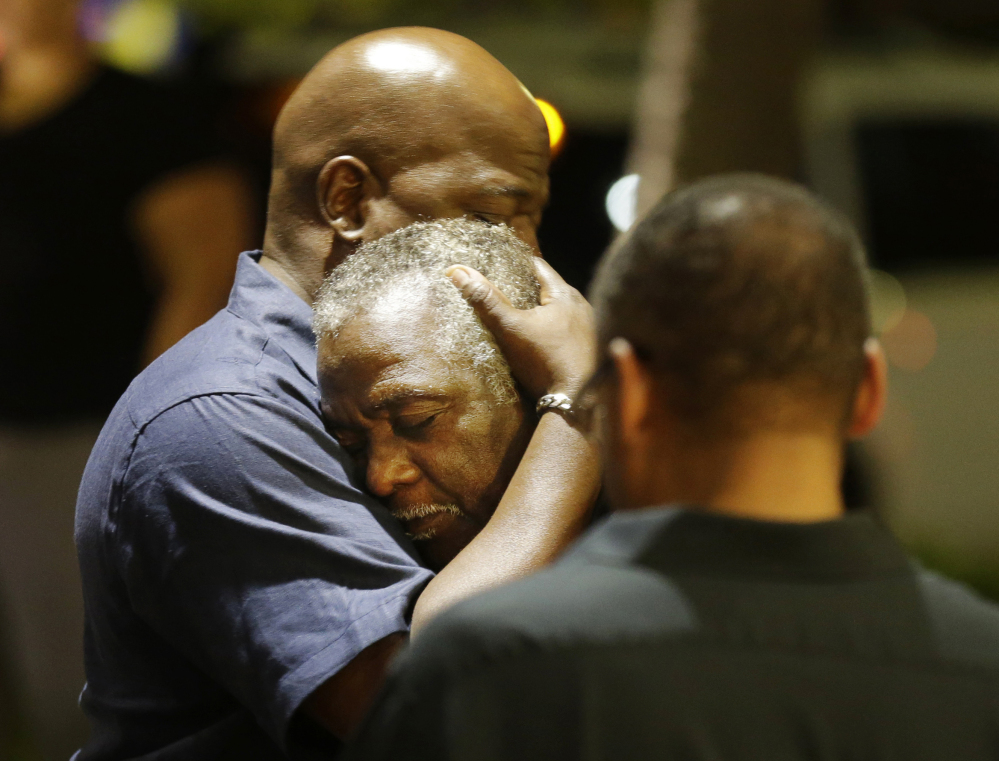 Worshippers embrace after a group prayer across the street from the scene of a shooting Wednesday night at Emanuel AME Church in Charleston, S.C. A white man opened fire during a prayer meeting inside the historic black church, killing nine people, including the pastor and three other clergy members, in an assault that authorities described as a hate crime.
