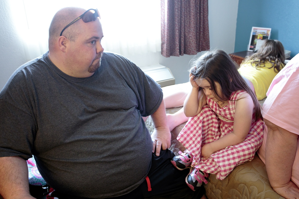Charles Needham tries to comfort his 3-year-old daughter, Alexis, in a room at the Super 8 Motel in Westbrook on Friday. The Needhams had to leave their apartment in Westbrook on Thursday night after city officials declared it unfit to live in. Needham said Alexis is confused by the move. Gabe Souza/Staff Photographer