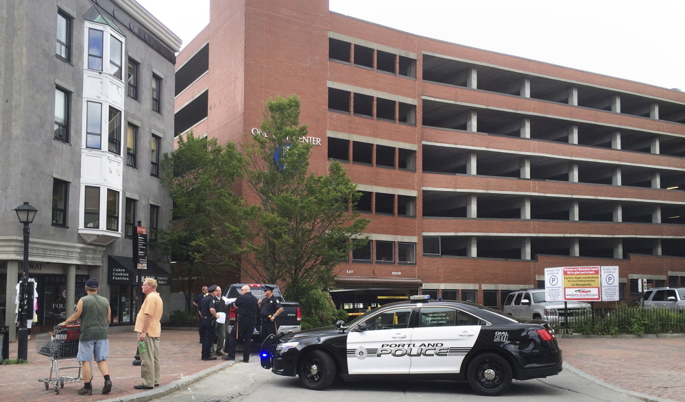 Police cars block the entrance to the One City Center parking garage in Portland on Friday afternoon. An man armed with a pistol robbed the Bank of America branch at One City Center and reportedly fled toward the garage. Police did not find the man in the garage. Gregory Rec/Staff Photographer