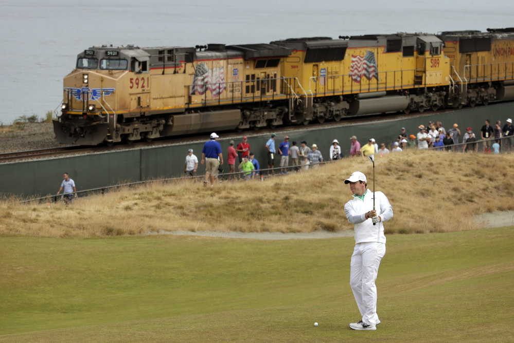 Rory McIlroy of Northern Ireland prepares to hit from the 16th fairway as a fright train rolls past during the first round of the U.S. Open golf tournament at Chambers Bay on Thursday in University Place, Wash.