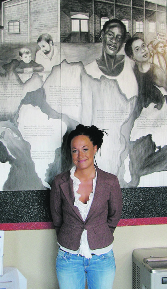 Rachel Dolezal in 2009, posing with a mural she painted at the Human Rights Education Institute in Coeur d'Alene, Idaho.
