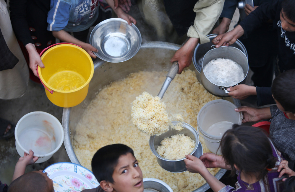 Afghan villagers hold out their plates for food donated by other villagers as they prepare to break their fast during the holy month of Ramadan in Kabul, Afghanistan, on Friday.