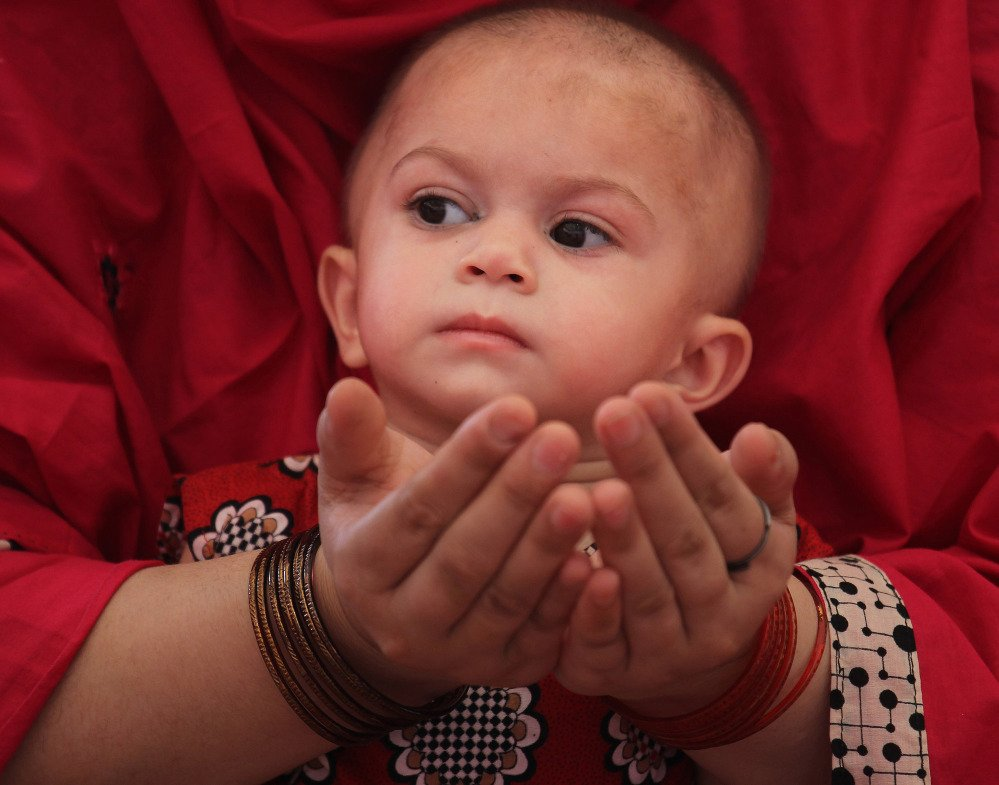 A Pakistani Muslim woman holds her child during Friday prayers at a mosque in Lahore, Pakistan, as Muslims around the globe observe Ramadan.