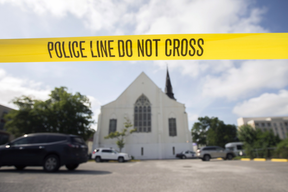 Police tape surrounds the parking lot behind the AME Emanuel Church as FBI forensic experts work the crime scene Friday.