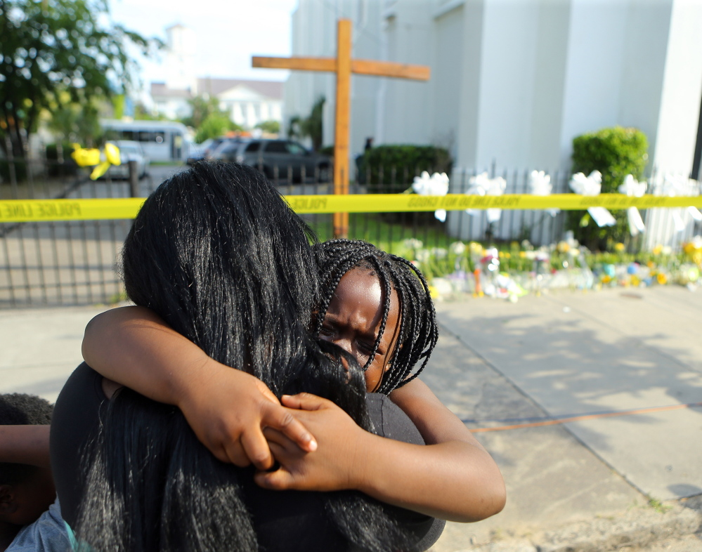 Kearston Farr hugs her 5-year-old daughter, Taliyah, as they visit a memorial for the nine shooting victims at the Emanuel AME Church in Charleston, S.C., on Friday.