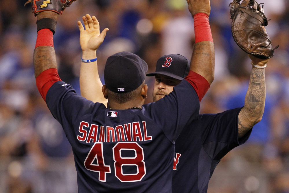 Boston's Mike Napoli celebrates with Pablo Sandoval at the end of Friday night's 7-3 win against the Kansas City Royals. Napoli drove in two runs with a single, and Sandoval doubled and singled.