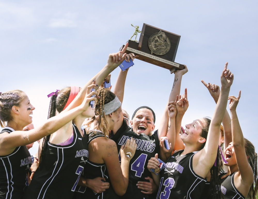 Marshwood players show off the championship trophy Saturday after capturing the school's first Class A girls' lacrosse state title with a 13-5 win over Messalonskee. Whitney Hayward/Staff Photographer