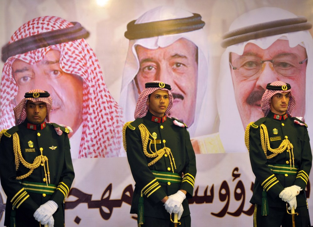 Saudi royal guards stand in front of portraits of King Abdullah bin Abdulaziz, right; Crown Prince Salman bin Abdulaziz, center; and Muqrin bin Abdulaziz in Riyadh, Saudi Arabia. Leaked documents reveal lavish expenditures of royals.