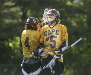 Owen Thoreck of Cape Elizabeth jumps with teammate Ben Shea after a goal for the Capers during their 7-5 victory against Yarmouth in the Class B boys' lacrosse state final Saturday at Fitzpatrick Stadium. Whitney Hayward/Staff Photographer