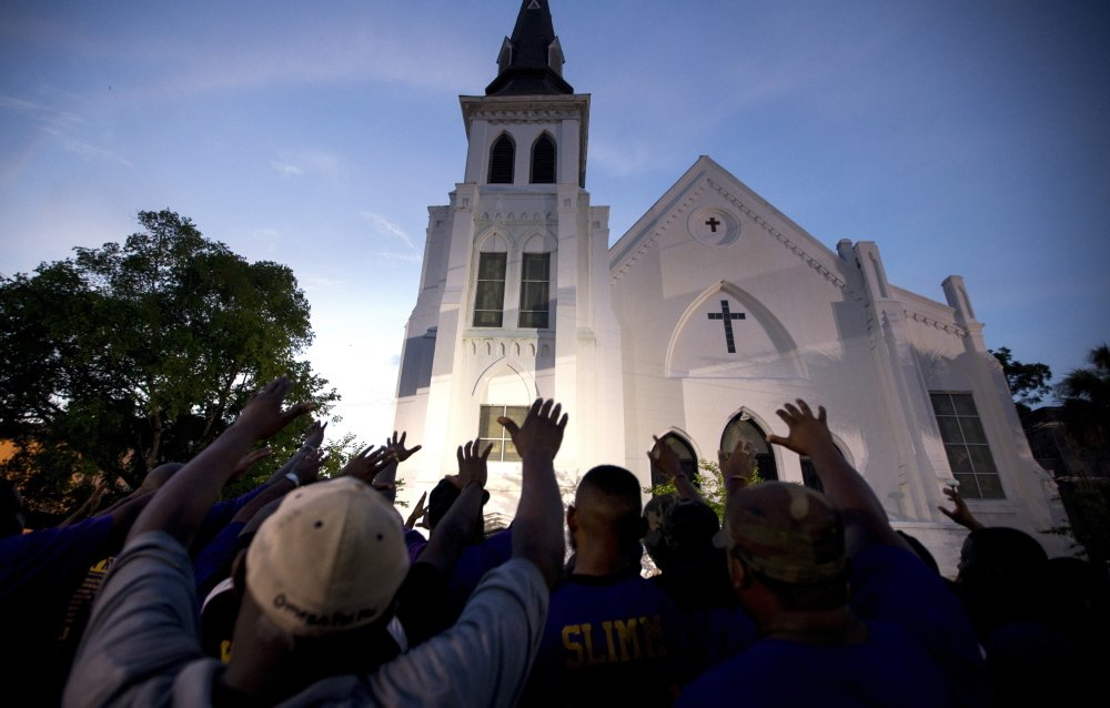 Members of the first international fraternal organization founded on a black campus, Omega Psi Phi, lead a prayer service outsie the Emanuel AME Church in Charleston, S.C., Friday, two days after the mass shooting.