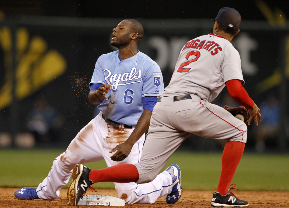 Kansas City Royals' Lorenzo Cain reacts after getting tagged out by Boston Red Sox shortstop Xander Bogaerts while attempting to advance to second base on a bad pitch in the third inning Sunday at Kauffman Stadium in Kansas City, Mo.