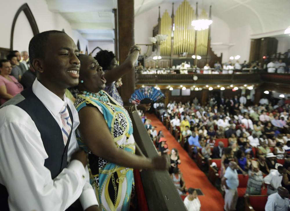 Parishioners Shakur Francis, left, and Karen Watson-Fleming sing at Sunday's service in Emanuel AME Church in Charleston, S.C., four days after a mass shooting killed nine people during a Bible study there.
