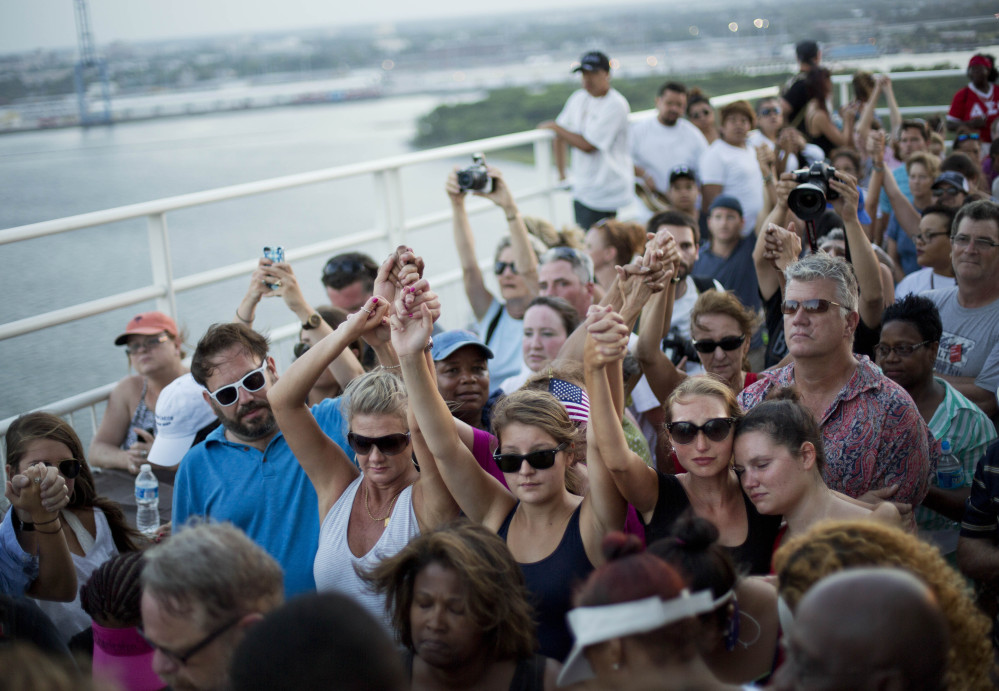 People join hands in a moment of silence as thousands of marchers meet on Charleston's main bridge Sunday evening in solidarity after the shooting deaths of nine black people last Wednesday allegedly by a self-described racist.
