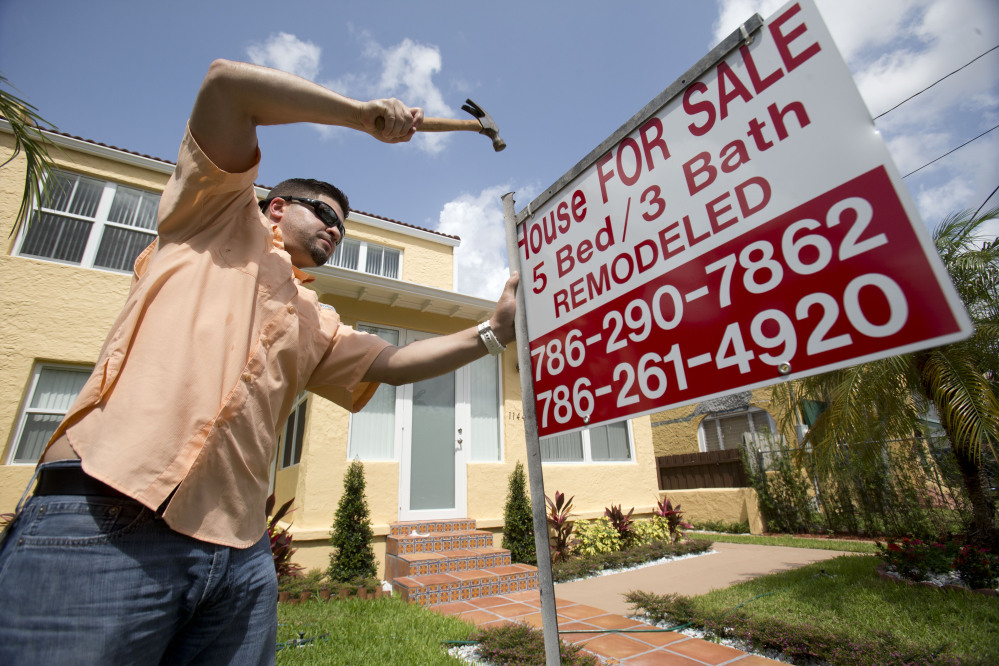 Robert Almirall, director of marketing and special assets coordinator for Mederos & Associates Real Estate Inc., puts up a sign in front of a home in Miami this spring.