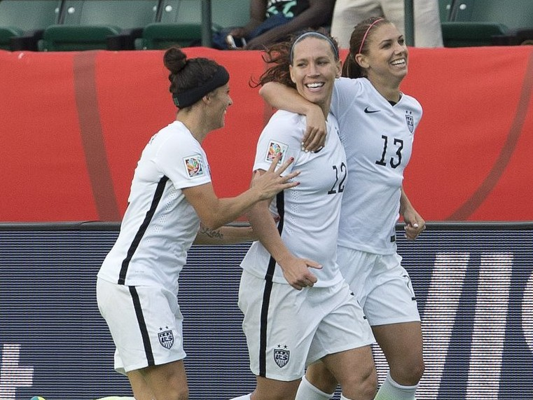 The United States' Ali Krieger (11), Lauren Holiday (12) and Alex Morgan (13) celebrate a goal against Colombia in second half Monday in Edmonton, Alberta.