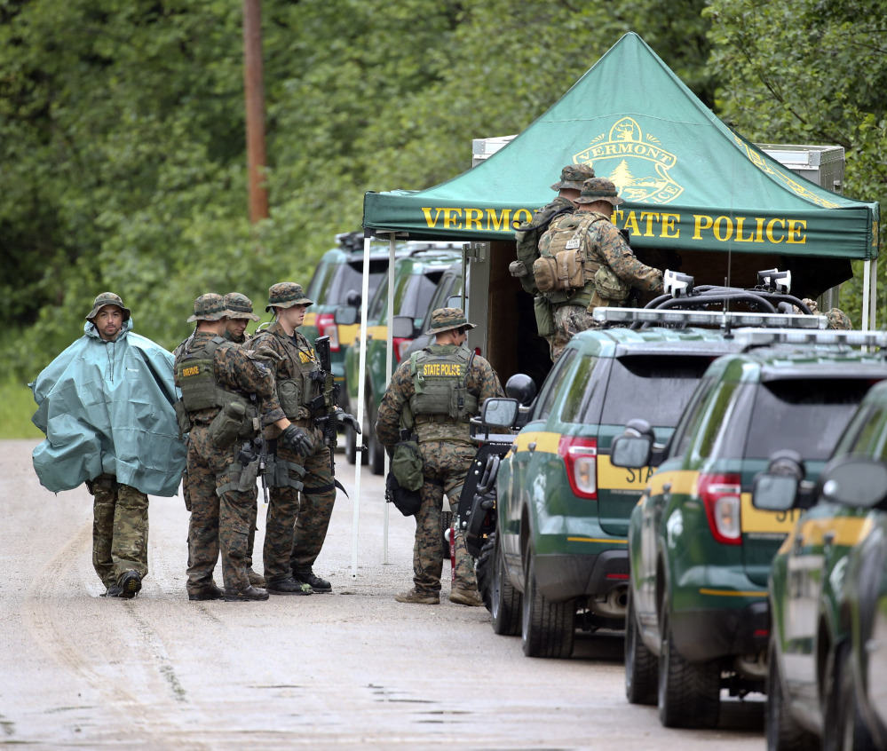 Law enforcement officers gather as the search continues for two escapees from Clinton Correctional Facility in Dannemora, on Tuesday, in Malone, N.Y.