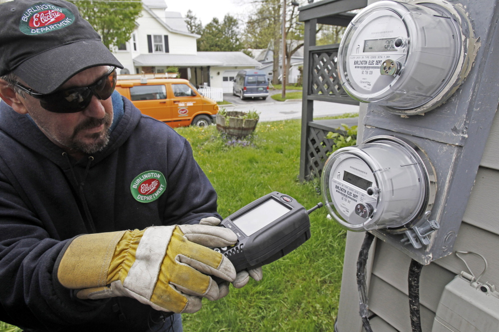 Mark Delbeck of Burlington Electric checks the radio frequency of a smart meter in Burlington, Vt. Home efficiency measures such as installing new windows or replacing insulation may actually cost homeowners money in the long run, according to the conclusion of a University of Chicago study.