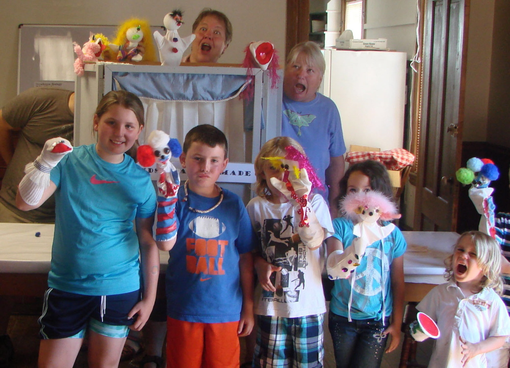 Deborah Beckwith-Noonan, at rear behind the puppet theater, goofs around with kids at a puppet workshop at the Canaan Farmers Hall. Noonan, who was injured in a car accident in March, died Sunday of her injuries.