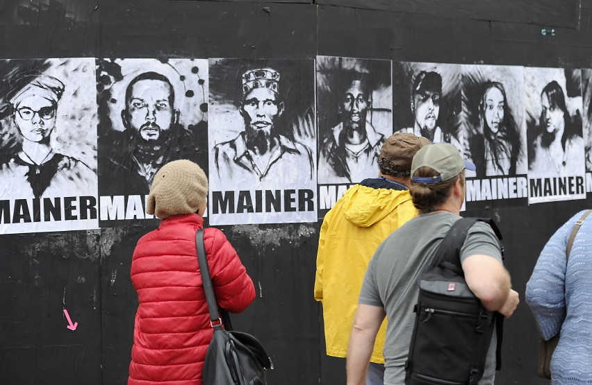 """A group of eight portraits that first appeared in May on a black plywood wall next to Congress Street has become part of the citywide conversation about whether Portland should continue providing aid to asylum seekers. The black-and-white portraits show eight men and women of different ethnic backgrounds, each labeled """"Mainer."""" The portraits bear the signature of Pigeon, a street artist."""