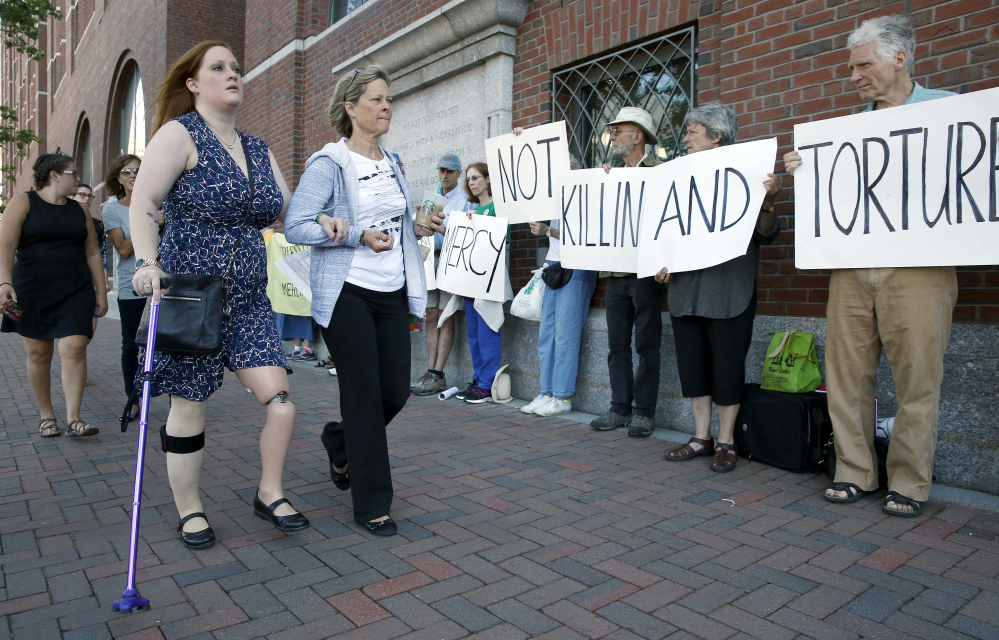 Boston Marathon bombing victim Erika Brannock, foreground left, and her mother Carol Downing, foreground right, walk past demonstrators outside federal court in Boston, on Wednesday. In court, 24 victims and family members of victims spoke of the impact that the Boston Marathon bombing has had on their lives.