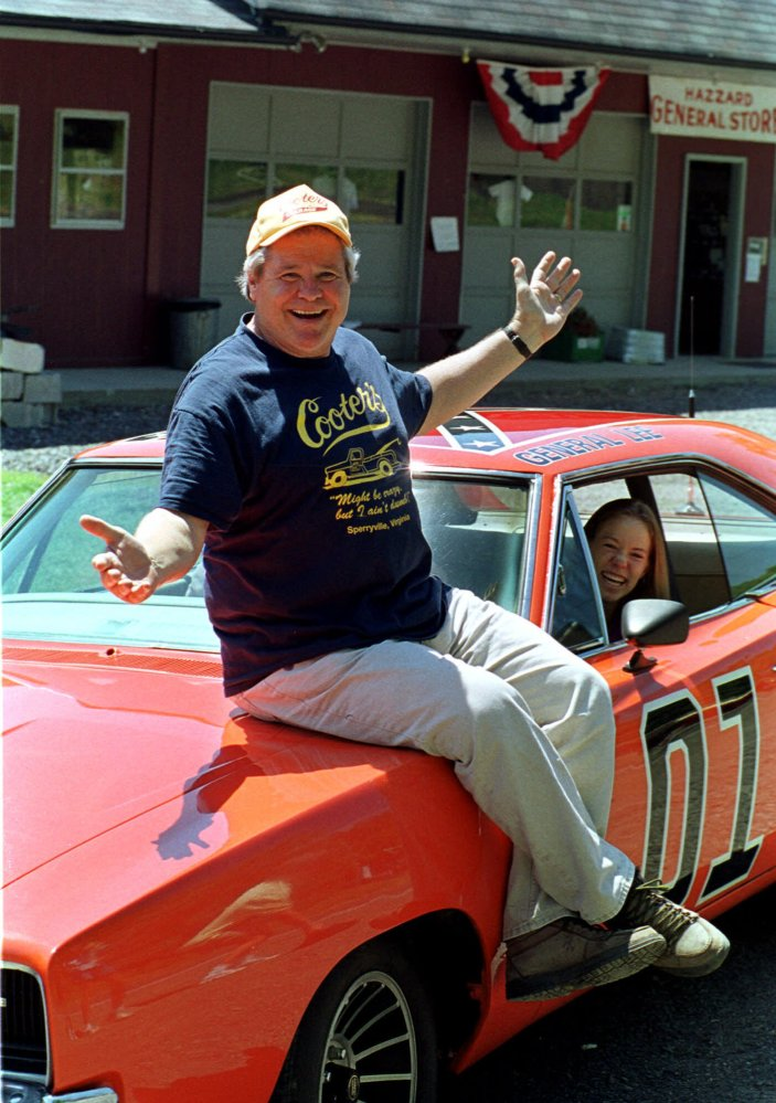 """In this Aug. 10, 1999, file photo, """"Cooter,"""" actor Ben Jones, sits atop one of the 229 hotrods, named the General Lee, used in the show """"Dukes of Hazzard"""" as ecstatic fan, Aliceson Johnson, of Charlottesville, Va., sits in the drivers seat in front of his store in Sperryville, Va."""