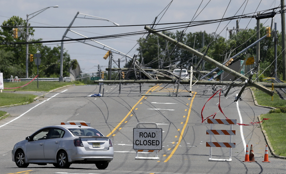 A driver turns her car at a closed road Wednesday after a violent storm downed poles and power lines Tuesday night in Gibbstown, N.J. Many were without power Wednesday.