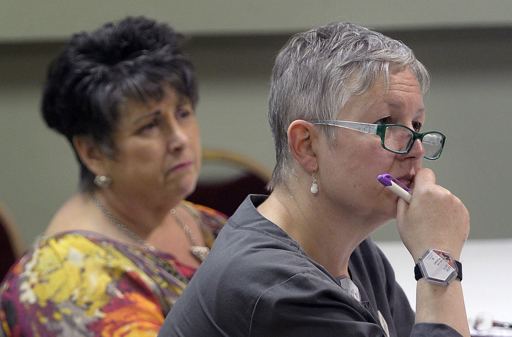 Tamlyn Osolin, left, of South Portland and Kathi Smith of Portland listens to Rev. Kenneth Lewis, pastor of Green Memorial A.M.E. Zion Church, Wednesday.