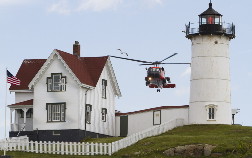 A U.S. Coast Guard helicopter hovers over Nubble Light as it searches for a missing person in the waters off Cape Neddick on Thursday.