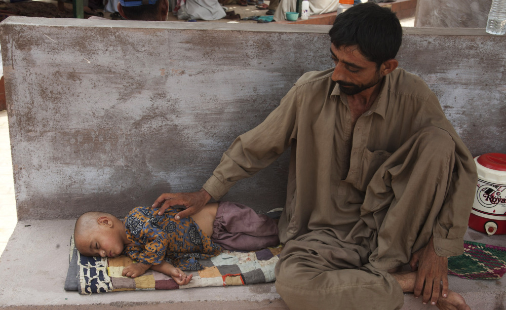 A father waits for medical help for his dehydrated daughter outside a ward at a children's hospital in Karachi, Pakistan,  on Wednesday.