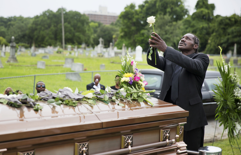 Gary Washington holds up a rose before placing it on the casket of his mother, Ethel Lance, one of the nine people killed in the shooting at Emanuel AME Church last week, after her burial service Thursday in Charleston, S.C. The Associated Press