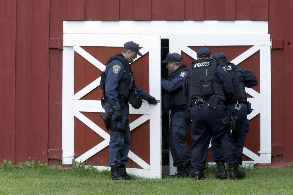 New York State Department of Corrections Officers search a barn in Owls Head, N.Y., for convicted murderers Richard Matt and David Sweat on Friday. Police shifted a focus of their three week search closer to the Canadian border.