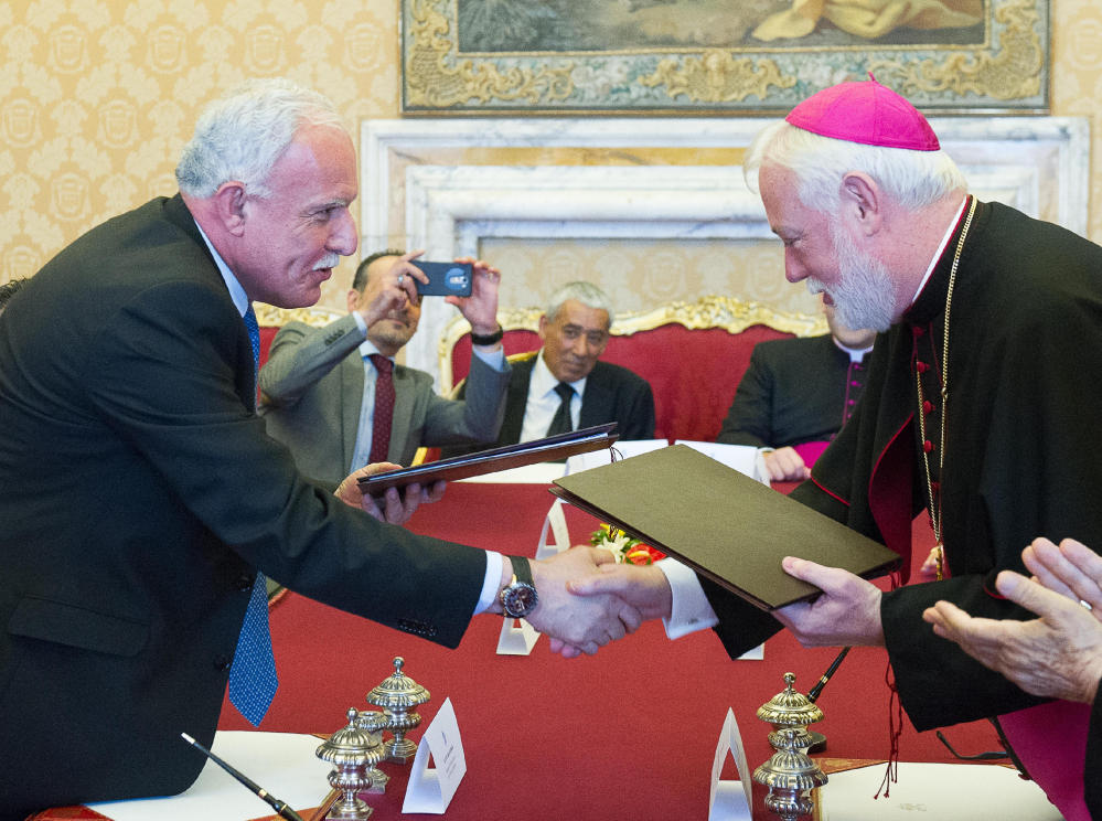 Vatican Foreign Minister Paul Gallagher, right, and his Palestinian counterpart, Riad al-Malki, shake hands after signing a treaty at a ceremony inside the Vatican.