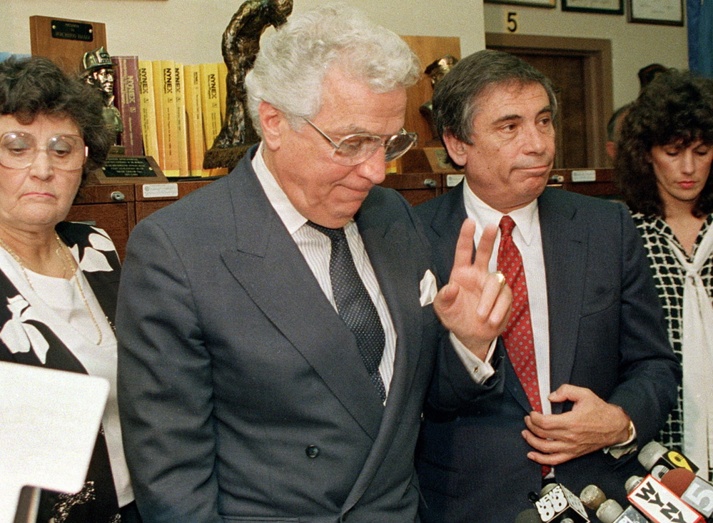 Mario Biaggi, second left, gestures to the media shortly after announcing his resignation from Congress on Aug. 8. 1988, at his headquarters in New York.