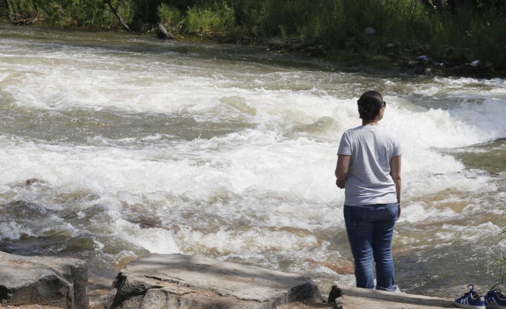 Clear Creek rushes past a woman in Golden, Colo., on Tuesday. Rapidly melting snow is sending Colorado's rivers racing out of the mountains. Some commercial operations are seeking calmer rapids and stocking extra safety gear.
