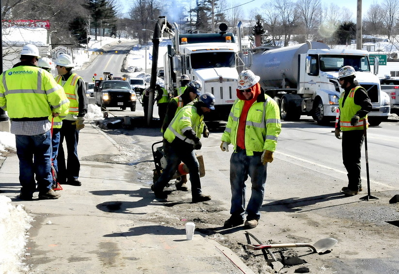 Employees of Summit Natural Gas of Maine and subcontractors work on the gas pipeline in the center of Norridgewock. The company is lowering its prices by 70 percent.