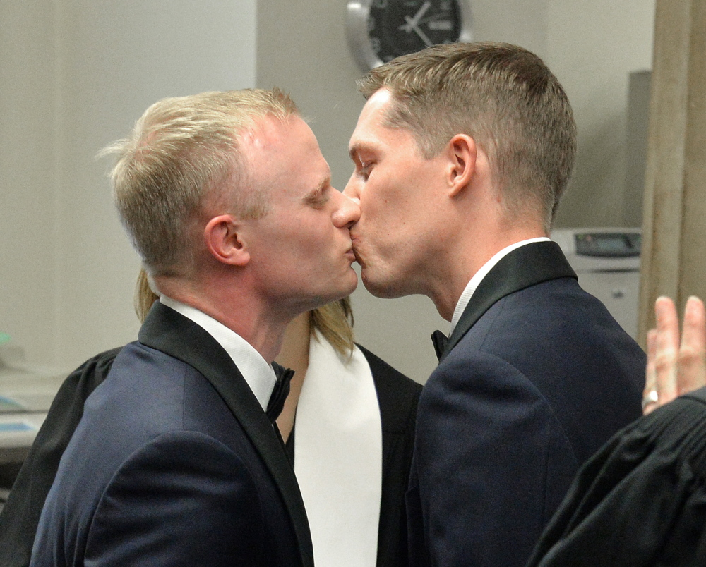 Benjamin Moore, left, and Tadd Roberts kiss after their marriage ceremony at the Jefferson County Clerks Office on Friday in Louisville, Ky. The Associated Press
