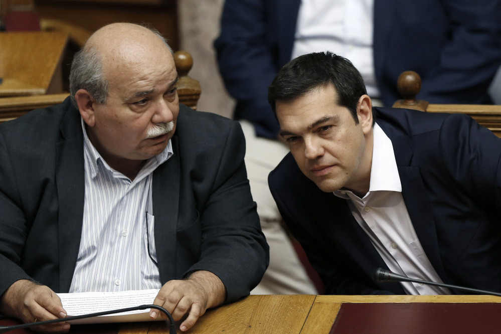 Greece's Prime Minister Alexis Tsipras, right, chats with Greek Minister of Interior and Administrative Reconstruction Nikos Voutsis during an emergency Parliament session for the government's proposed referendum in Athens on Saturday.