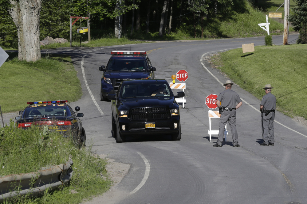 New York State officers stand at the road block at the perimeter of the search area for convicted murderer David Sweat on Saturday in Malone, N.Y.