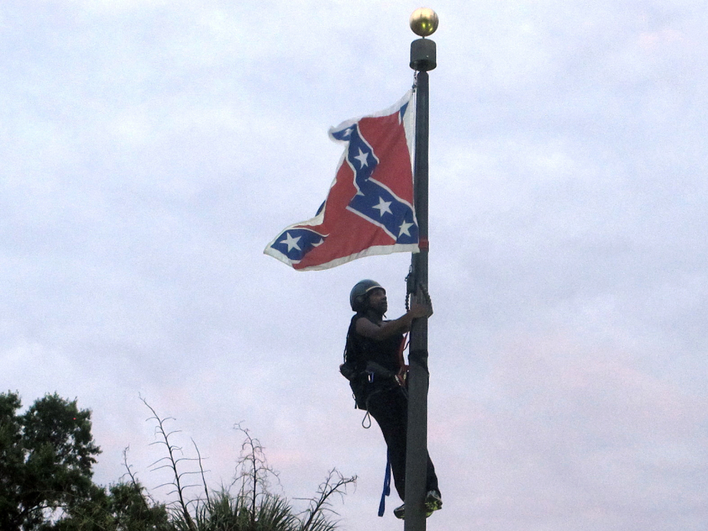Bree Newsome of Charlotte, N.C., climbs a flagpole to remove the Confederate battle flag at a Confederate monument in front of the Statehouse in Columbia, S.C., on Saturday. She was taken into custody when she came down. The flag was raised again by capitol workers about 45 minutes later.  (AP Photo/Bruce Smith)