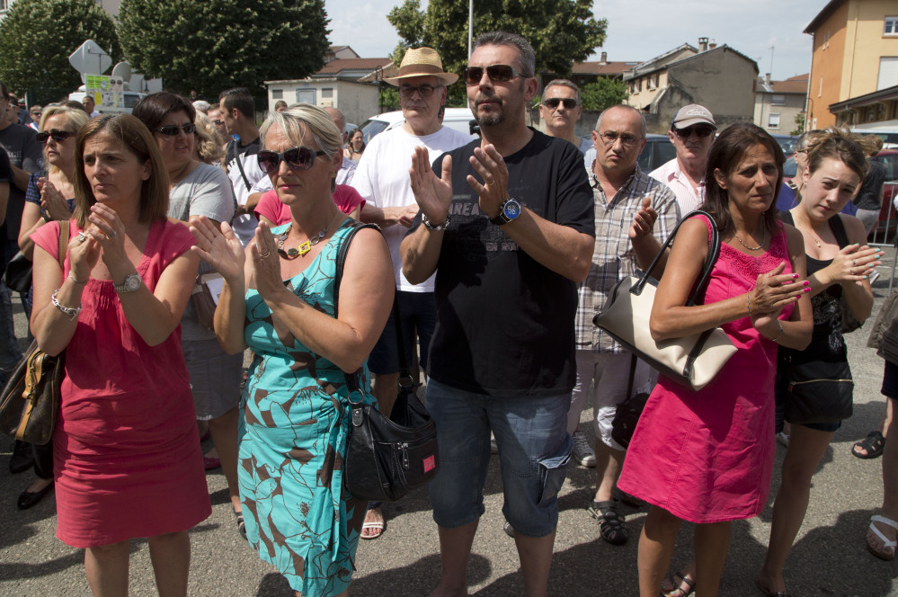 People applaud after a moment of silence in Quentin-Fallavier, southeast of Lyon, France, on Saturday to pay their respects to the victim of the attack that took place Friday.