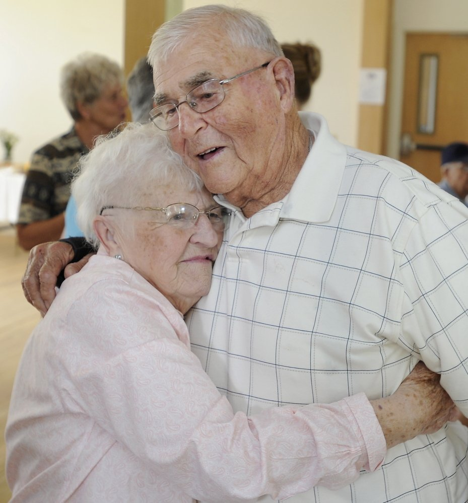 Oland Morton gets a big hug from his wife, Violet, as they celebrate their 70th wedding anniversary with family and friends in their hometown of Gorham.