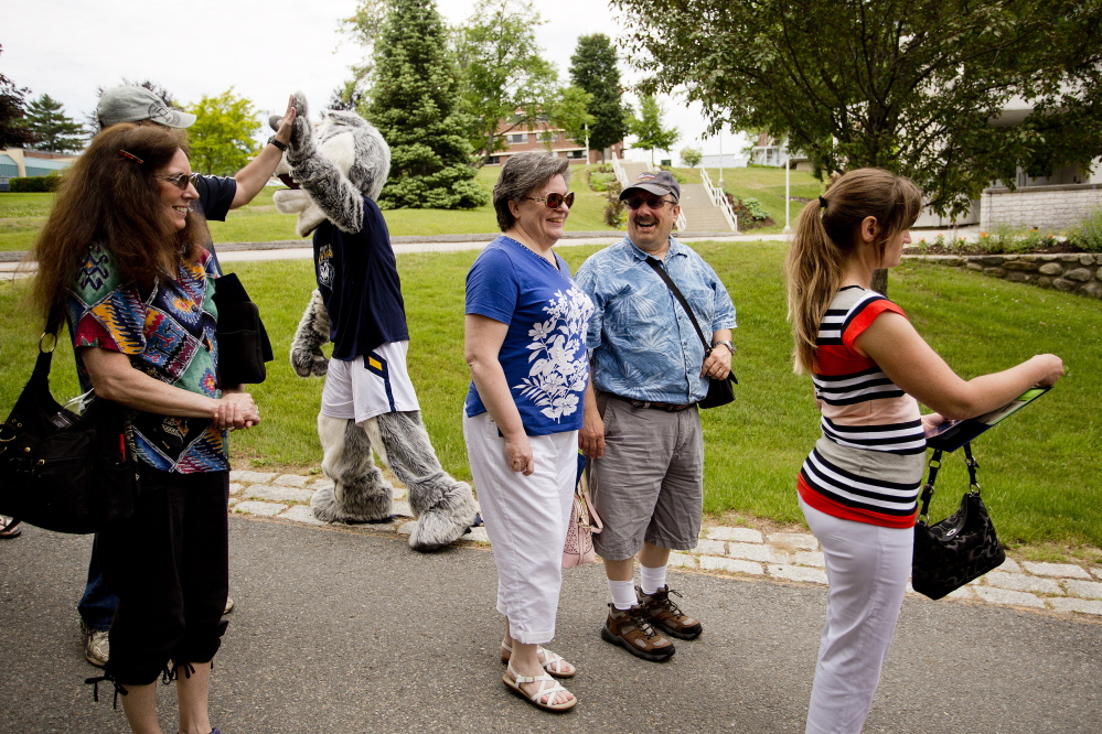 The Balsamos – Carolyn and Tony of Saco – chuckle after getting a high five from the University of Southern Maine's mascot, Champ the Husky, during their son Robert's orientation process recently. The Balsamos have struggled to save for school for their four children.