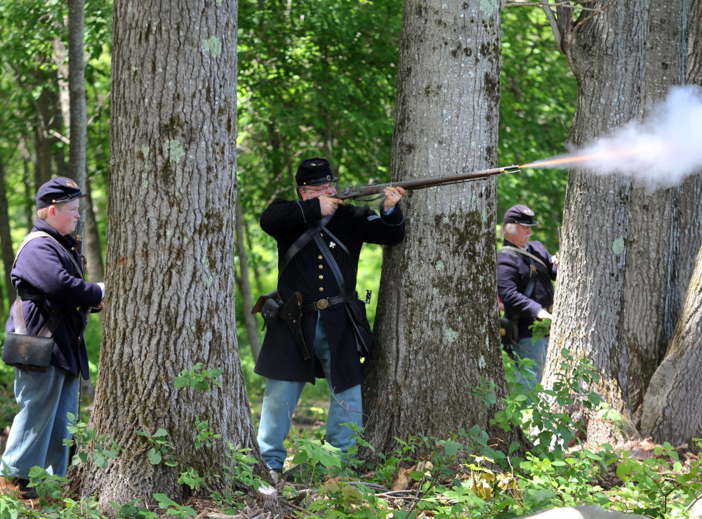 Tom Connell, of the 15th Massachusetts Volunteer Infantry re-enactment group, fires his musket at Confederate troops Saturday during a Civil War re-enactment at Viles Arboretum in Augusta.