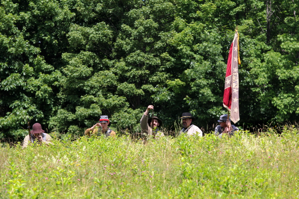 Confederate Civil War re-enactors reload their muskets during a skirmish with Union troops during a Civil War re-enactment at Viles Arboretum in Augusta on Saturday.
