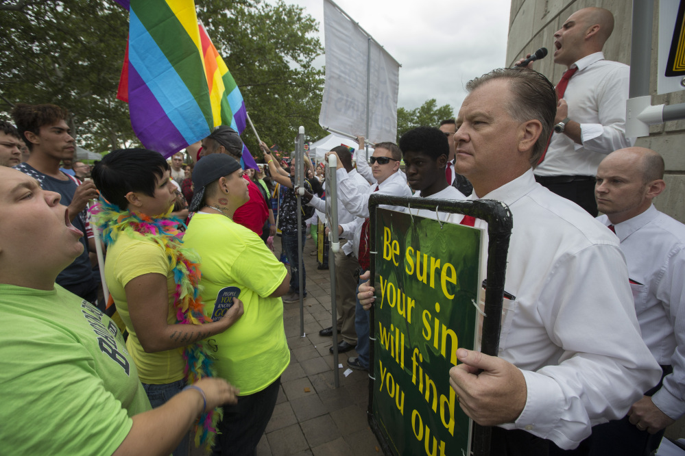 People protesting same-sex marriage picket at the Cincinnati Pride festival on Saturday in Cincinnati. While same-sex marriage is now protected, many states are without laws to prevent discrimination based on sexual orientation in other realms.