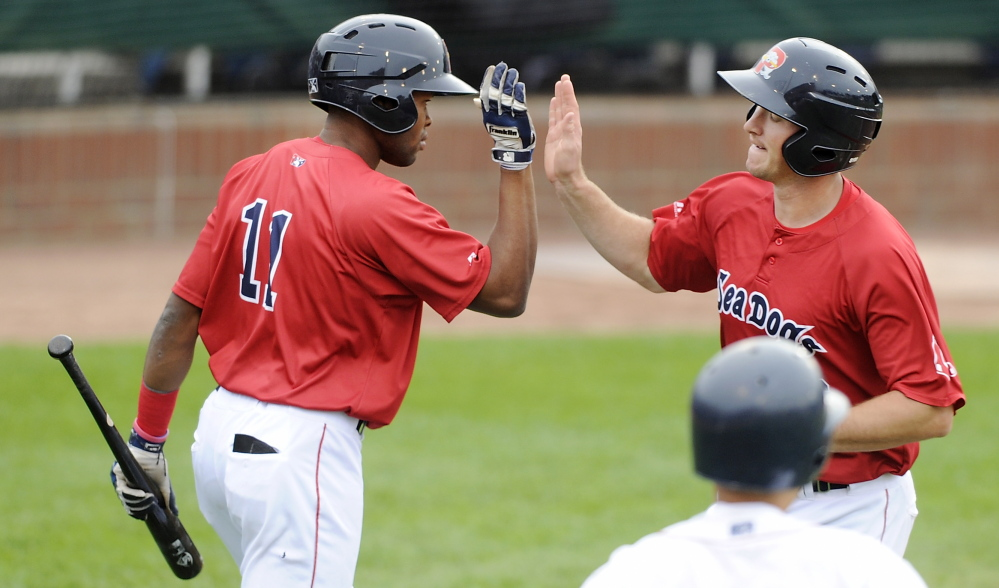 Jantzen Witte, right, gets a high-five from Manuel Margot after scoring the Sea Dogs' first run. Witte led off the second inning with a triple and scored on a sacrifice fly by Sam Travis.