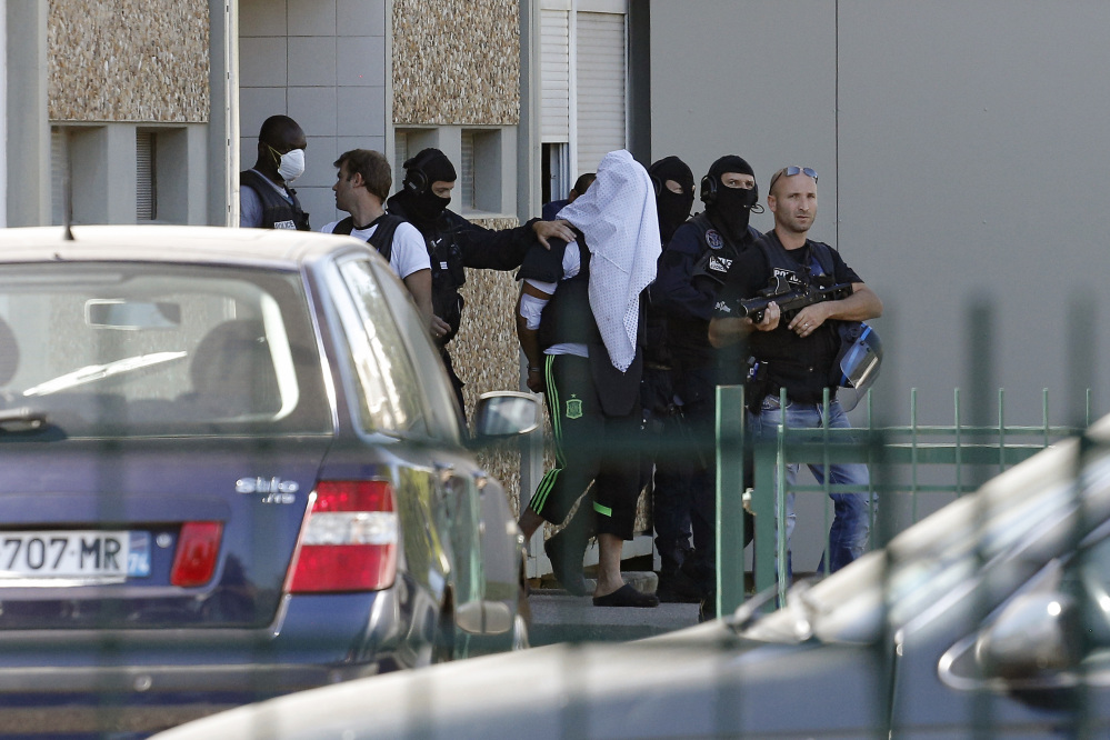 The suspect in the beheading of a businessman, Yassine Salhi, a towel over his head to mask his face, is escorted by police officers as they leave his home in Saint-Priest, outside the city of Lyon, central France, on Sunday.